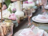 a chic and romantic Valentine's Day wedding table with blush and pink floral arrangements, candles in gold candleholders, white and blush plates, gold cutlery