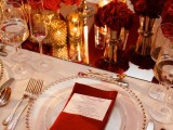 a refined white, red and gold Valentine's wedding tablescape with a shiny table runner, burgundy napkins, glam gold vases and candleholders and red roses