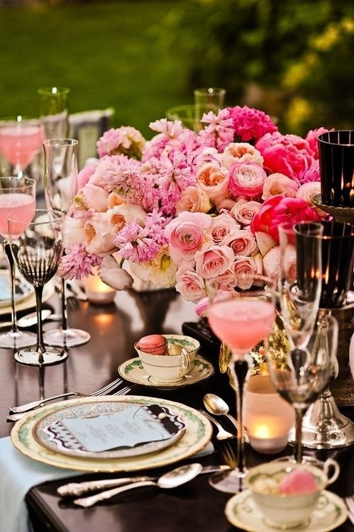 a beautiful and refined Valentine's Day wedding table with printed plates, blush and hot pink blooms, gold touches and printed goblets