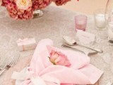 a sweet and romantic Valetine's Day wedding table with a printed tablecloth, a pink glass charger and light pink linens, a chic bold pink and mauve floral arrangement is beautiful