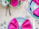 a super bright Valentine's Day wedding table with a silver tablecloth, hot pink napkins, electric blue plates, hot pink and bright blue blooms is ultra-modern