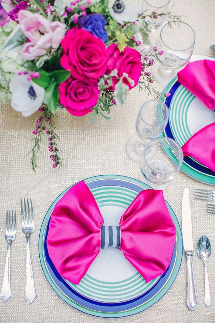 a super bright Valentine's Day wedding table with a silver tablecloth, hot pink napkins, electric blue plates, hot pink and bright blue blooms is ultra modern
