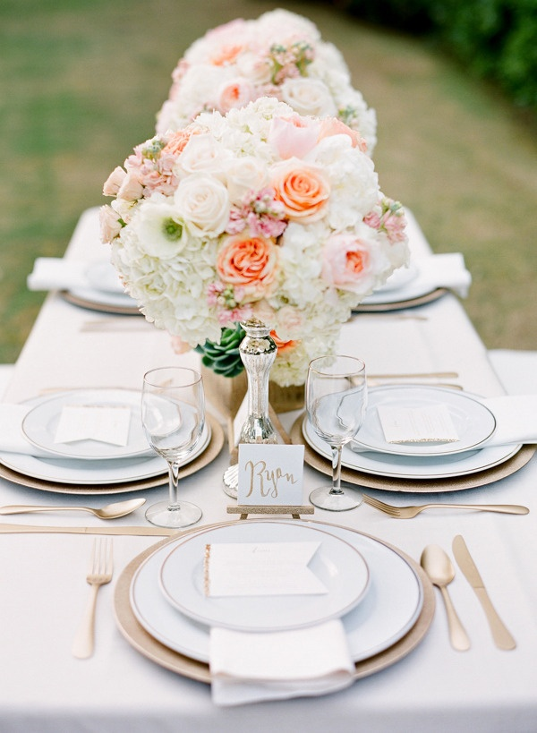 an elegant Valentine's Day wedding tablescape with chic white linens, blush blooms, peachy touches and gold rimmer plates and chargers