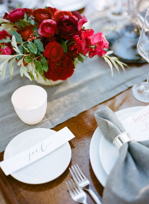 an elegant Valentine's Day wedding tablescape with grey linens, metallic napkin rings, white porcelain, a bold red and burgundy floral arrangement