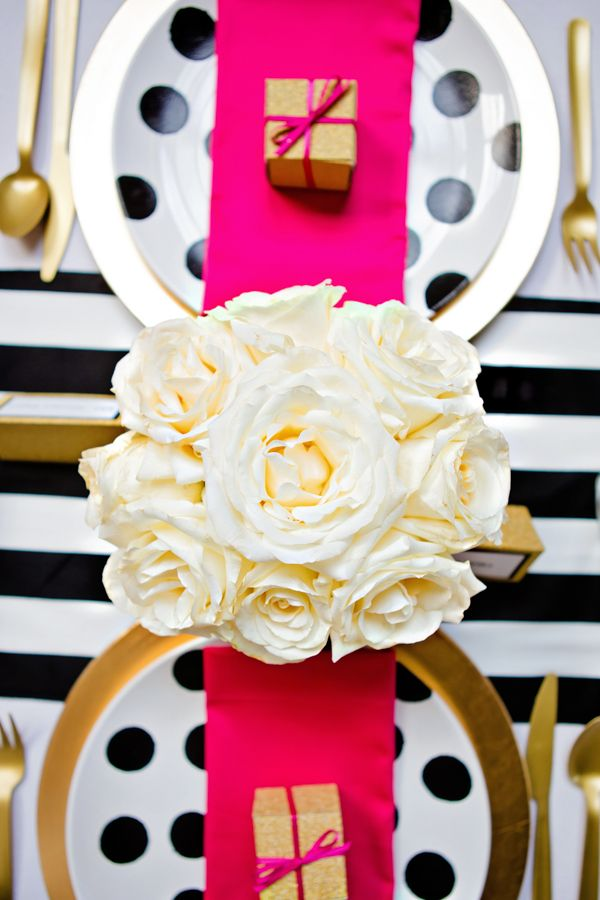 a modern glam Valentine's Day wedding table with a striped tablecloth, gold chargers, white rosesm hot pink napkins and polka dot plates