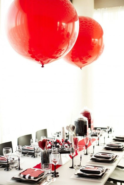 a black, white and red Valentine's Day wedding tablescape with black and white porcelain, a red runner and red balloons, striped and red napkins