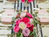 an elegant and glam Valentine's wedding table with a striped runner, gold chargers and cutlery and pink napkins plus bold pink, fuchsia and lavender bloom arrangements
