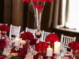 a bold black, white and red Valentine's wedding table with black runners, red napkins, petals and blooms, neutral candles and crystal glasses
