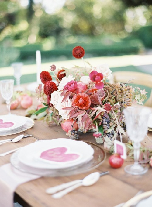 a pretty Valentine's Day wedding tablespace with an uncovered table, some blush and red blooms, fruits and dried leaves, sheer plates and hearts on each place setting