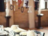 an elegant wedding tablescape with neutral linens, black planters with white blooms, metallic chargers and silver cutlery, an overhead installation with photos and letters for Valentine's Day