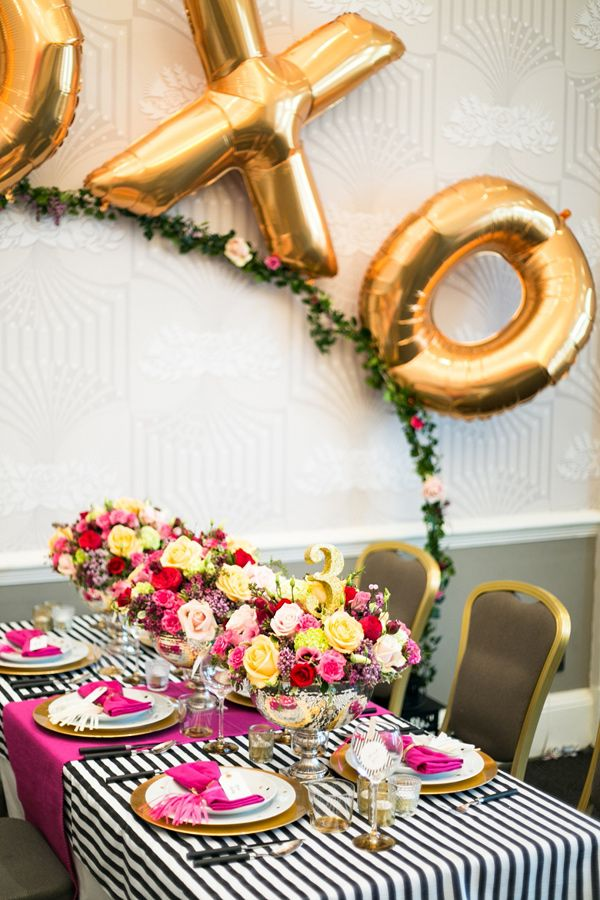 a bold Valentine's Day wedding tablescape with a striped tablecloth, bold fuchsia table runners and napkins, bold floral arrangement, a greenery arch with gold XO letters