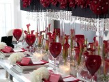a super glam and refined white and red Valentine's Day wedding table with white blooms and red callas, red glasses, white porcelain and red linens, lamps with red blooms and crystals