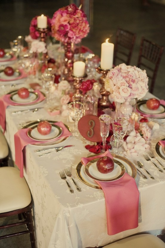 a romantic blush, pink and white Valentine's Day wedding tablescape with a vintage tablecloth, gold rimmed chargers and cutlery, blush adn pink blooms in balls, candles and a refined floral table runner
