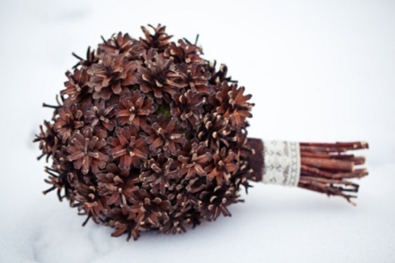 a stylish winter wedding bouquet of pinecones only and a chic ribbon wrap is non typical and very cool