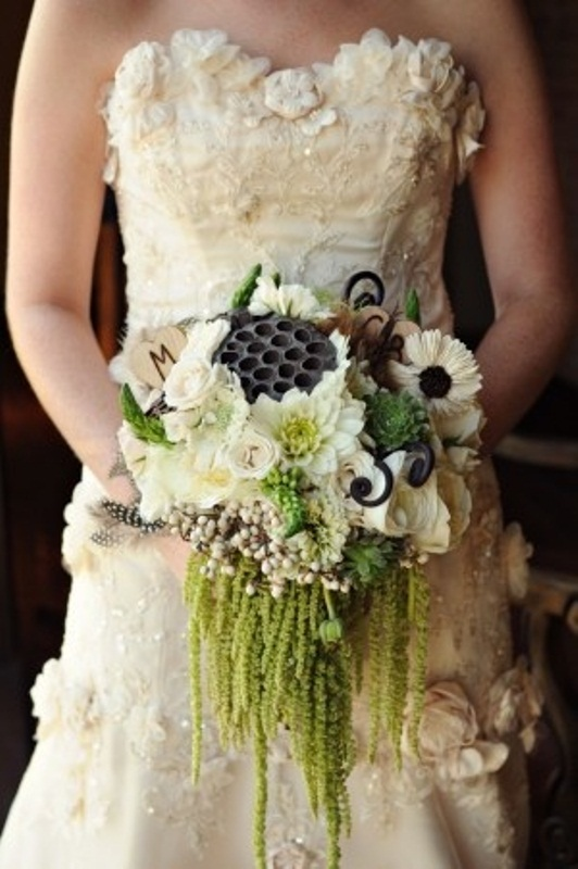 a white and green winter wedding bouquet with berries, lotus seeds and cascading elements plus feathers