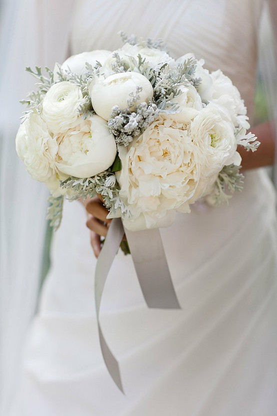a frozen looking winter wedding bouquet with white blooms and pale greenery plus silver ribbons