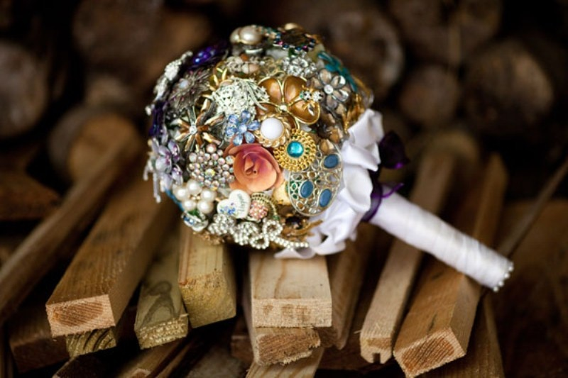 a colorful brooch wedding bouquet with a white ribbon wrap is a cool alternative to a usual one