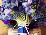 a bold purple and blue wedding bouquet with a navy wrap and a large button for your 'something blue' at the wedding