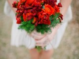 a red winter wedding bouquet with evergreens is a bold holiday wedding idea
