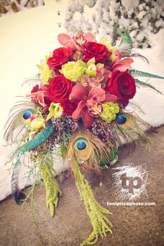a bright and colorful winter wedding bouquet with red, yellow and green blooms plus peacock feathers for a bold touch