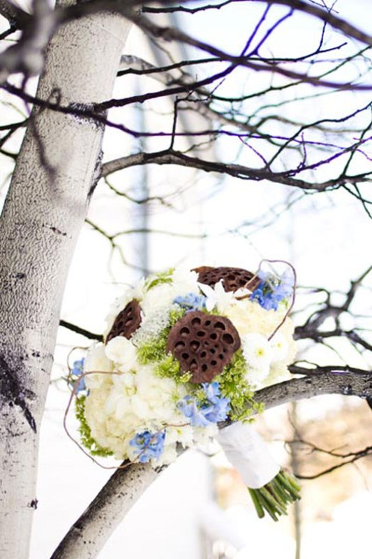 a winter wedding bouquet of blue and white blooms, with lotus seeds plus green hydrangeas and white ribbons