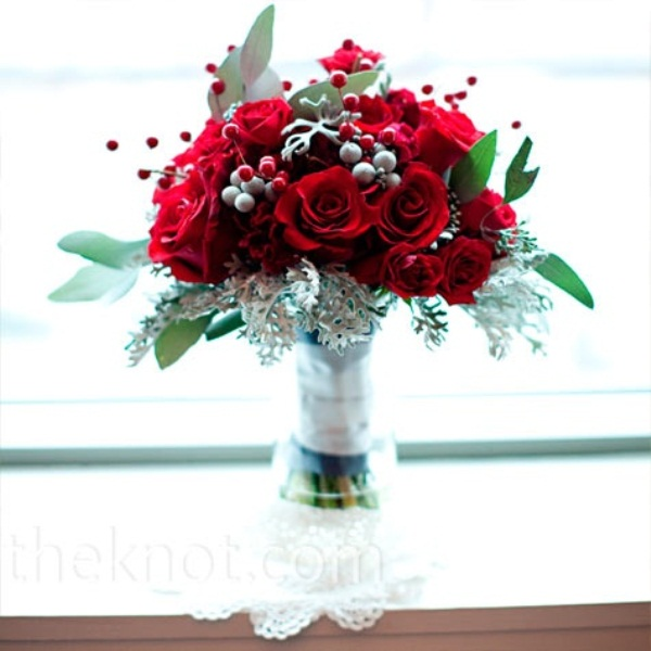 a red winter wedding bouquet with pale greenery, foliage and berries plus a white wrap for a contrast