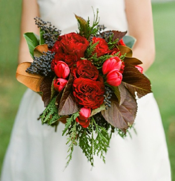 a bold red winter wedding bouquet with berries, evergreens and dark foliage for a colorful touch