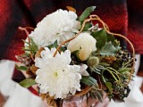 a romantic rustic wedding bouquet with white blooms, greenery and some thistles and vine