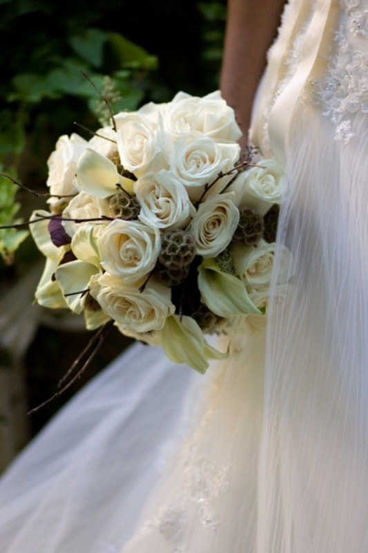 a white winter wedding bouquet with white roses and callas, twigs is a cool idea with a rustic feel