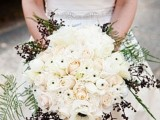 a winter wedding bouquet with lots of roses, berries and ferns is a luxurious and chic idea