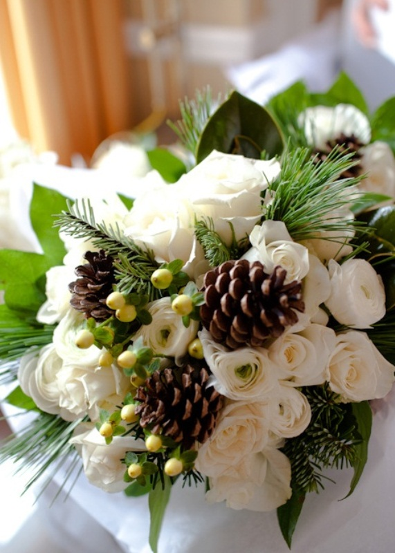 a rustic winter wedding bouquet with white blooms, greenery, berries and pinecones