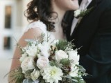 a cchic winter wedding bouquet with white and blush blooms, greenery and twigs is a stylish option