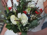 a textural winter wedding bouquet with white blooms, red and blue berries, foliage and much texture