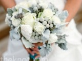 a pale winter wedding bouquet of foliage, blooms and berries looks frozen and very cold