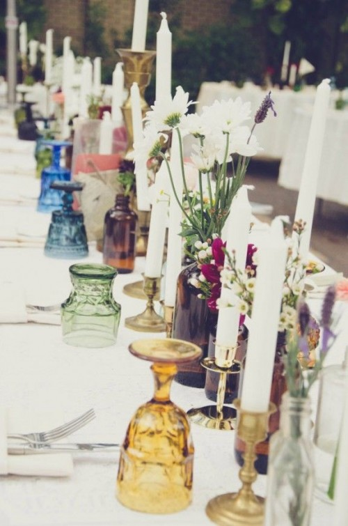 a wedding table setting with candles, dark bottles with blooms, colored glasses for a boho feel