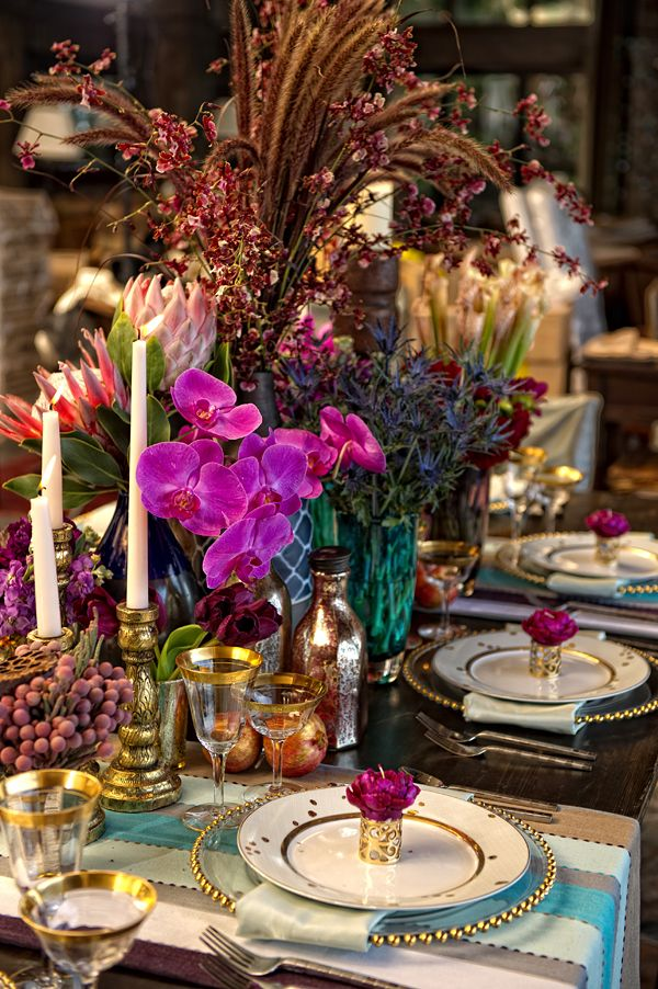a super colorful tablecloth, bright blooms and vases, striped textiles, gold rim glasses