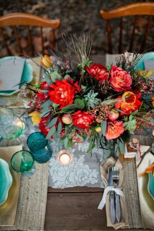a bright tablescape with a lace tablecloth, burlap placemats, turquoise plates and glasses plus colorful blooms