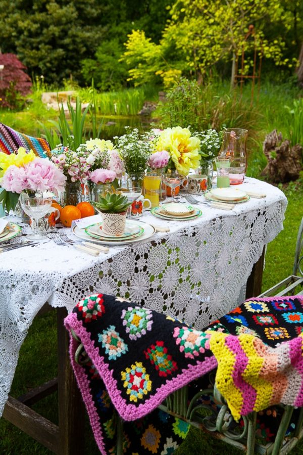 a boho meets vintage tablescape with a macrame tablecloth, bright blooms and fruits, colorful plates and cups