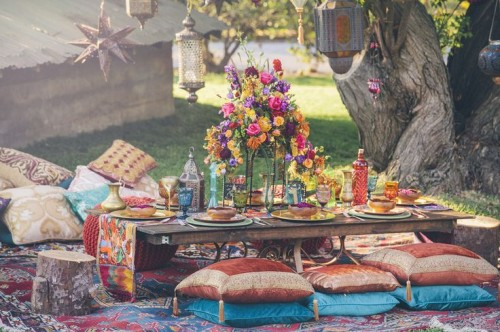 a bright picnic setting with a low table, pillows, rugs, a colorful floral centerpiece, colored candles and glasses