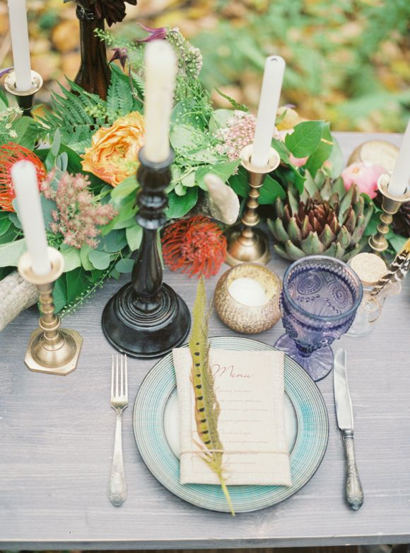 a boho table setting with an aqua plate, colored glasses, a bright floral and greenery centerpiece and lots of candles