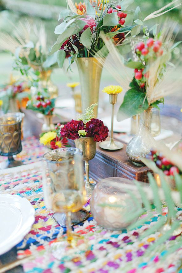 a bright boho tablescape with colorful placemats, colored glasses and super bright florals and herbs