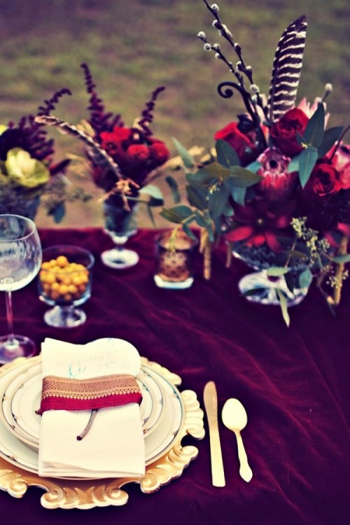 a bright boho tablescape with a burgundy tablecloth, a catchy charger and bold blooms with feathers