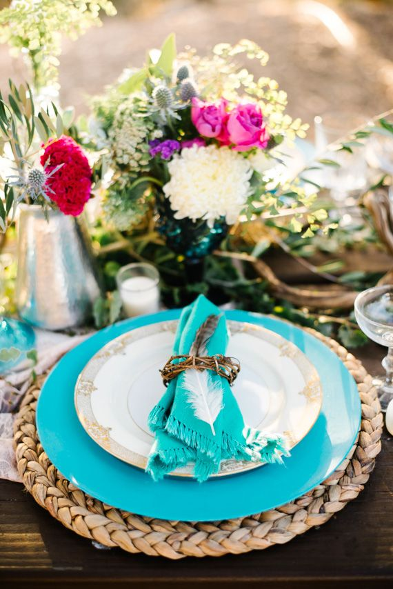 a colorful tablescape with turquoise plates, a wicker charger, bright florals in metallic vases