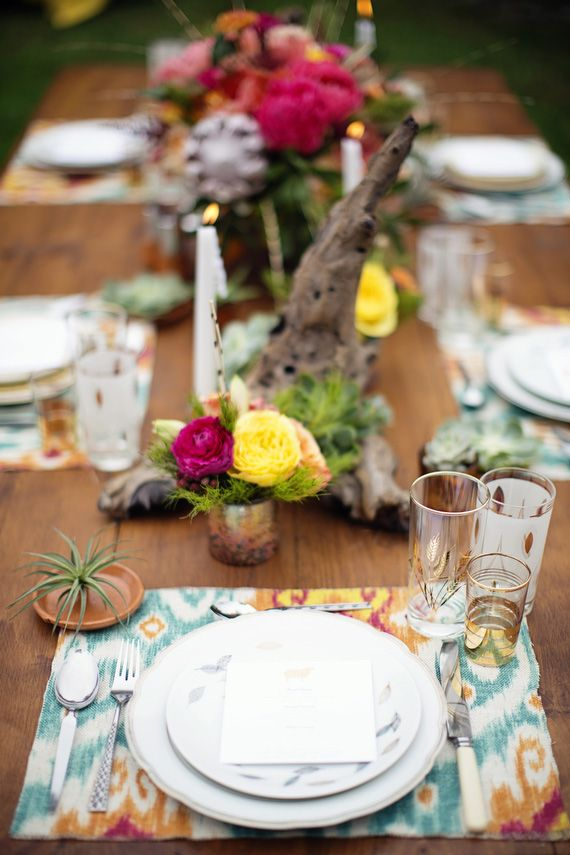 a bright tablescape with colorful placemats, driftwood, colorful florals, candles and air plants