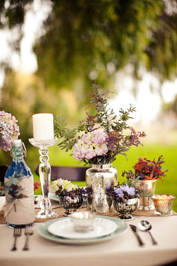 colorful blooms and foliage in vases, a urlap table runner and cutlery