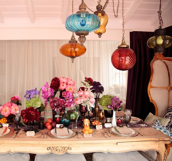 a colorful tablescape with bright lamps hanging down, colorful florals, fruits and colored glasses