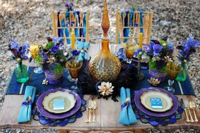 a super colorful tablescape done in purple and turquoise, bright gold touches, colored glasses and plates and lush florals