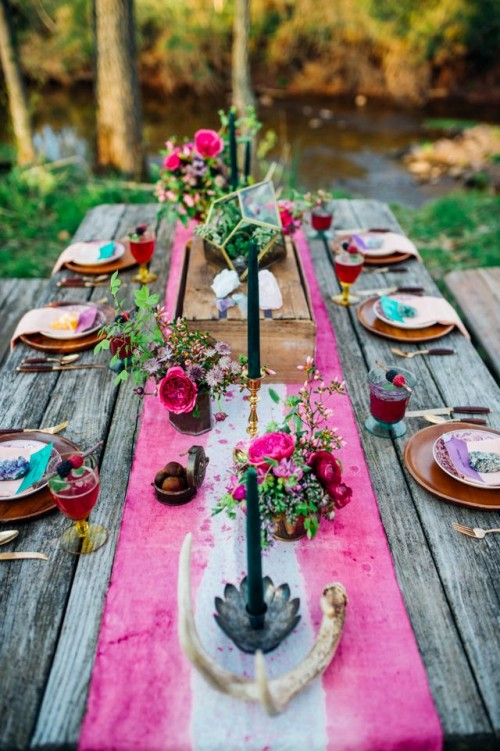 a super bright boho chic wedding tablescape with a tie dye table runner, antlers, colorful blooms and a terrarium plus bright cards