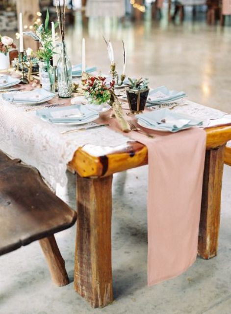 a boho tablescape with blush textiles, a lace tablecloth, greenery and blooms in planters and terrariums