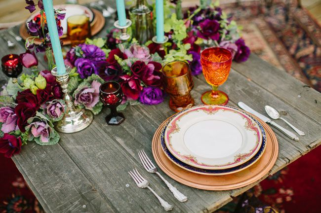 a colorful tablescape with bright florals, glasses, candles and gilded plates and chargers